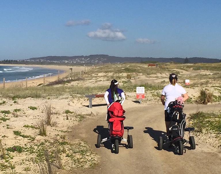 同伴プレーヤーと海沿いの砂浜カート道を歩く